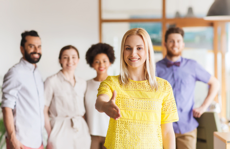 black businessman: business, startup, people, gesture and teamwork concept - happy young woman greeting by handshake over creative team in office