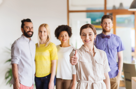gestures: business, startup, people, gesture and teamwork concept - happy young woman showing thumbs up over creative team in office Stock Photo