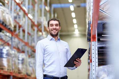 wholesale, logistic, business, export and people concept - happy man or manager with clipboard at warehouse