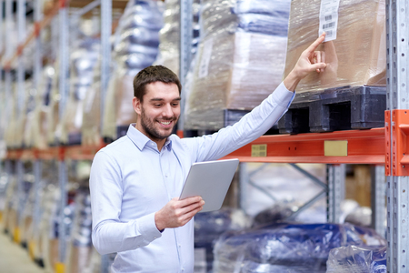 wholesale: wholesale, logistic, business, export and people concept - happy man or manager with tablet pc computer checking goods at warehouse Stock Photo