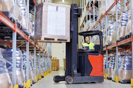elevator operator: wholesale, logistic, loading, shipment and people concept - man or loader with tablet pc computer and forklift or loader loading boxes at warehouse