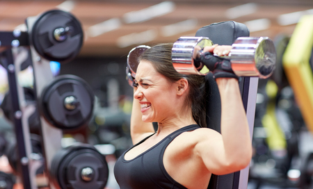 trabajando duro: deporte, fitness, culturismo, levantamiento de pesas y el concepto de la gente - mujer joven con mancuernas flexionando los músculos en el gimnasio de la parte posterior