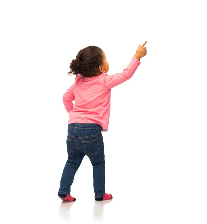 people, race, ethnicity and childhood concept - happy african american baby girl pointing finger to something from back