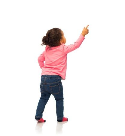 pueblo, raza, etnia y concepto de infancia - bebé feliz del afroamericano que señala el dedo a algo de la parte posterior