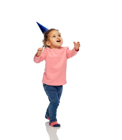 white party: childhood, fashion, birthday, holidays and people concept - happy smiling african american little baby girl with birthday party hat playing and catching something