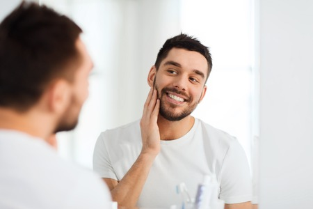 smiling young man: beauty, hygiene and people concept - smiling young man looking to mirror at home bathroom
