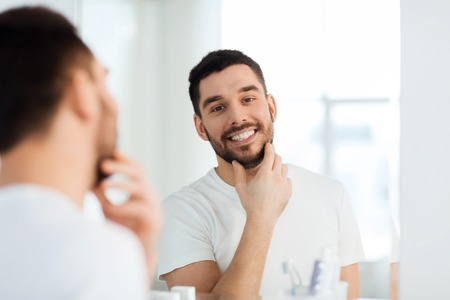 daily room: beauty, hygiene and people concept - smiling young man looking to mirror at home bathroom