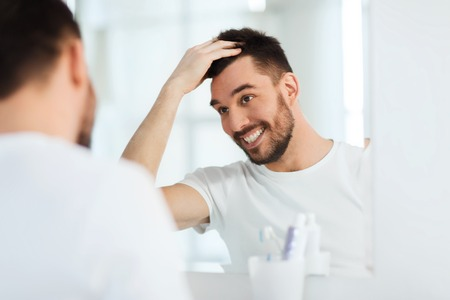 male hair: beauty, hygiene, hairstyle and people concept - smiling young man looking to mirror and styling hair at home bathroom