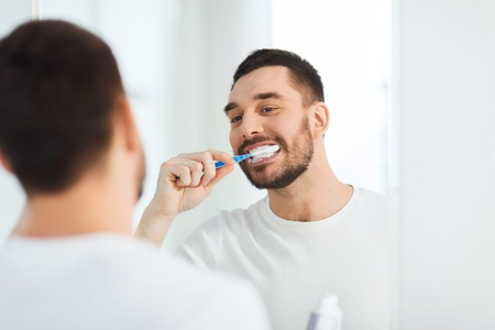 health care, dental hygiene, people and beauty concept - smiling young man with toothbrush cleaning teeth and looking to mirror at home bathroom Standard-Bild