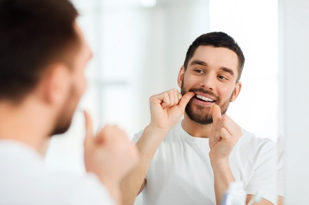 cuidado de la salud, higiene dental, las personas y el concepto de belleza - hombre joven sonriente con los dientes de limpieza de hilo dental y que mira al espejo en el cuarto de baño casero