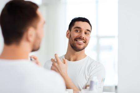 perfumería, belleza y concepto de la gente - hombre joven y sonriente feliz con perfume que mira al espejo usando olor en el baño