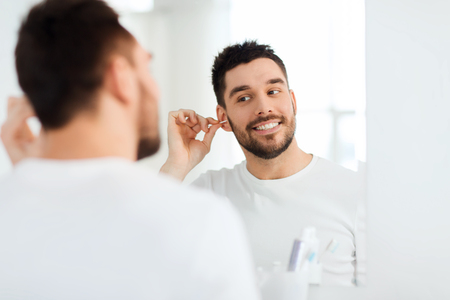 hygiene: beauty, hygiene and people concept - smiling young man cleaning ear with cotton swab and looking to mirror at home bathroom