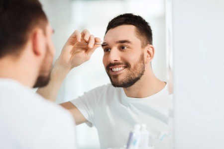tweezing eyebrow: beauty and people concept - smiling young man with tweezers tweezing eyebrow and looking to mirror at home bathroom Stock Photo