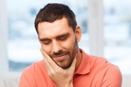 dolor de muelas: las personas, la salud, la odontología y el concepto de problema - hombre infeliz que sufren dolor de muelas en el hogar Foto de archivo