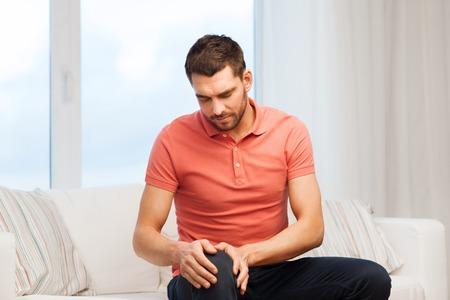 piernas: las personas, la salud y el concepto de problema - hombre infeliz que sufre de dolor en las piernas en el hogar Foto de archivo