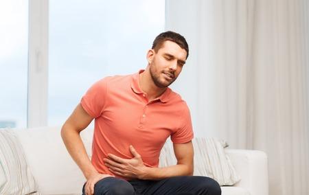 dolor de estomago: las personas, la salud y el concepto de problema - hombre infeliz que sufre de dolor de estómago en el hogar Foto de archivo