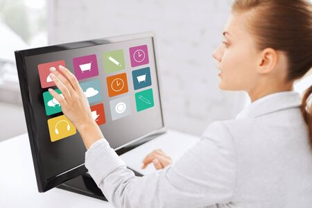 application icons: business, people, technology and media concept - woman with application icons on computer touchscreen in office