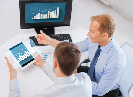 business, technology, statistics, economics and people concept - businessmen with charts on tablet pc and computer at office