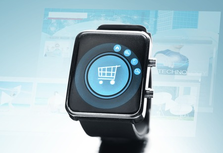 watch over: modern technology, object and media concept - close up of black smart watch with shopping cart on screen over blue background Stock Photo