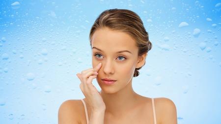 Schönheit, Menschen, Kosmetik, Hautpflege und Gesundheit Konzept - junge Frau Anwendung Creme auf ihr Gesicht über Wassertropfen auf blauem Hintergrund
