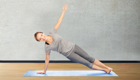 plank: fitness, sport, people and healthy lifestyle concept - woman making yoga in side plank pose on mat over room or gym background