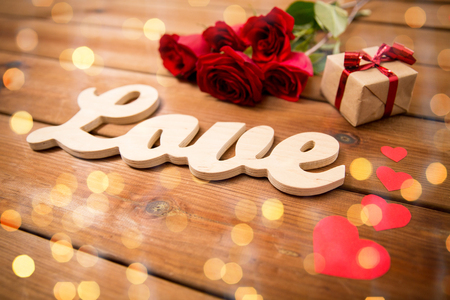flirtation: love, romance, valentines day and holidays concept - close up of gift box, red roses and hearts on wood over lights background Stock Photo