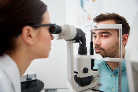 health care, medicine, people, eyesight and technology concept - optometrist with non contact tonometer checking patient intraocular pressure at eye clinic or optics store Stockfoto