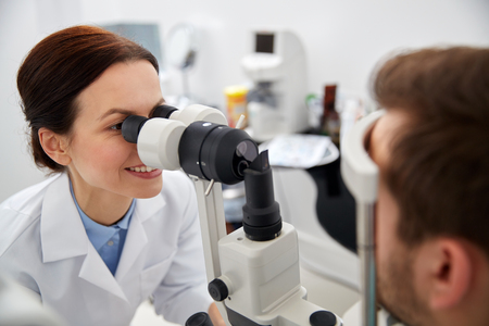 indentation: health care, medicine, people, eyesight and technology concept - optometrist with non contact tonometer checking patient intraocular pressure at eye clinic or optics store Stock Photo