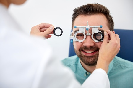 health care, medicine, people, eyesight and technology concept - optometrist with trial frame checking patient vision at eye clinic or optics store Stock Photo