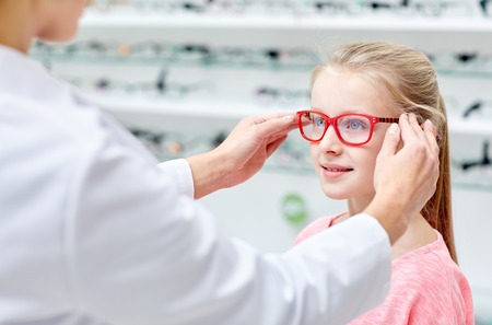 health care, people, eyesight and vision concept - optician putting glasses to little girl eyes at optics store Archivio Fotografico