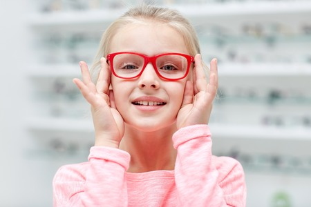 glasses eye: health care, people, eyesight and vision concept - little girl in glasses at optics store Stock Photo