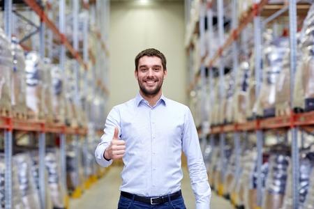 groothandel, logistiek, business, export en mensen concept - gelukkig man in het magazijn zien thumbs up gebaar