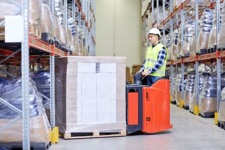 elevator operator: wholesale, logistic, loading, shipment and people concept - man or loader with forklift or loader loading boxes at warehouse