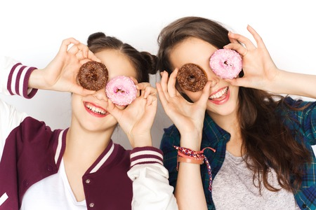 niña comiendo: personas, amigos, adolescentes y concepto de la amistad - Feliz sonriente bonita de las muchachas adolescentes con rosquillas haciendo muecas y divertirse