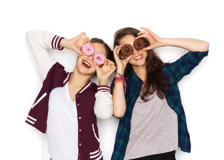 nice food: люди, друзья, подростков и концепция дружбы - Счастливые улыбающиеся девушки довольно подростки с пончики, делая лица и получать удовольствие Фото со стока