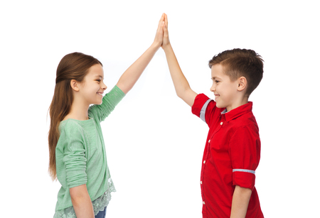 childhood, fashion, gesture and people concept - happy smiling boy and girl making high five Stock Photo