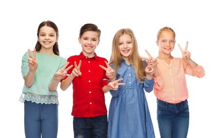 la infancia, la moda, la amistad y el concepto de la gente - muchacho sonriente feliz y niñas que muestran la muestra de la mano de la paz