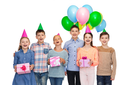 children birthday: childhood, holidays, friendship and people concept - happy smiling children in party hats with gifts and balloons on birthday Stock Photo