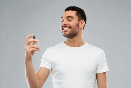 perfumery: perfumery, beauty and people concept - happy smiling young man with male perfume over gray background Stock Photo