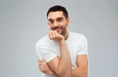 expresiones faciales: expresión y concepto de la gente - hombre sonriente feliz sobre fondo gris