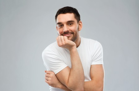 white men: expression and people concept - happy smiling man over gray background Stock Photo