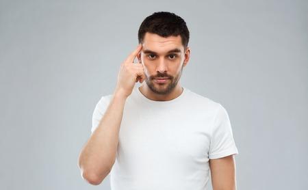 Werbung, Idee, Inspiration und Menschen Konzept - Mann zeigt mit dem Finger auf seinen Tempel über grauem Hintergrund Standard-Bild
