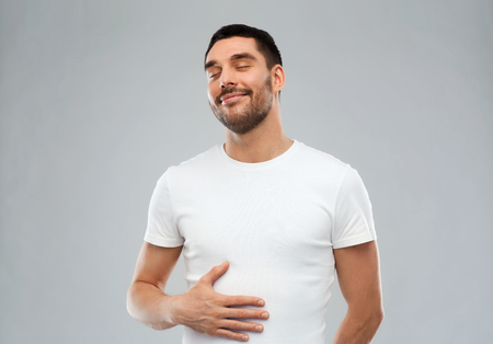 satisfied people: satisfaction and people concept - happy full man touching his tummy over gray background