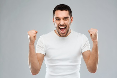emocje, sukces, gest i koncepcja ludzie - młody człowiek świętuje zwycięstwo nad szarym tle
