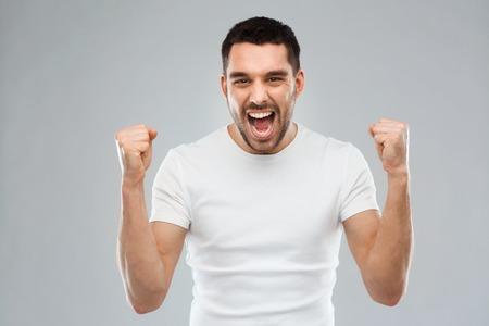 enojo: la emoción, el éxito, el gesto y el concepto de la gente - hombre joven que celebra la victoria sobre fondo gris