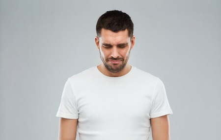 white man: emotion, sadness and people concept - unhappy young man over gray background Stock Photo