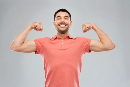 man power: power, fitness, strength, sport and people concept - happy smiling young smiling man showing biceps over gray background