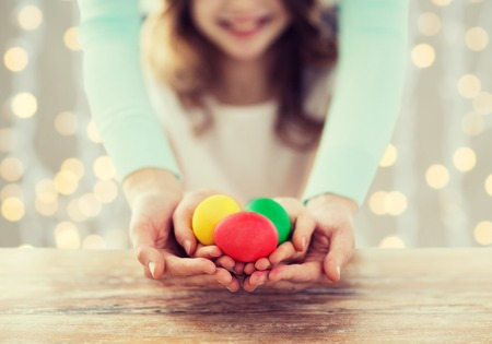 familia cristiana: Pascua, familia, gente, fiestas y la infancia concepto - de cerca de una niña feliz y madre manos que sostienen los huevos de colores sobre fondo de las luces