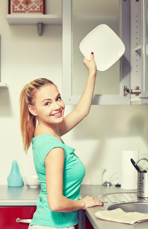 kitchen cabinets: people, housework and housekeeping concept - happy woman putting plate to kitchen cabinet Stock Photo