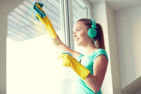 cleanser: people, housework and housekeeping concept - happy woman in headphones listening to music and cleaning window with cleanser at home